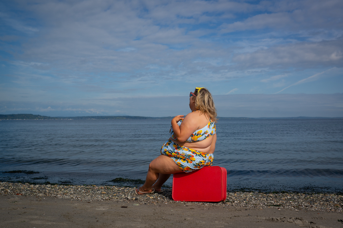 A fat blonde woman in a bikini with visible side rolls sits on a vintage red suitcase at the edge of the water on a beach, looking away.