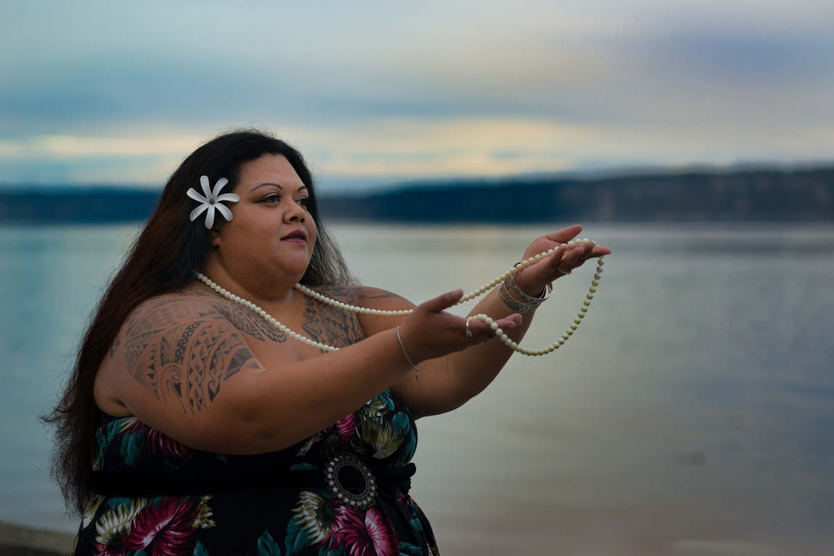 In this fine art photograph, a fat woman with brown skin and long black hair, wearing a sleeveless floral dress and a flower in her hair, is shown from the waist up. She's holding up one end of a long strand of pearls, with the other end of the necklace draped around her neck. Behind her is a body of water at dusk with low mountains in the background and a hint of sunset color in a cloudy sky.