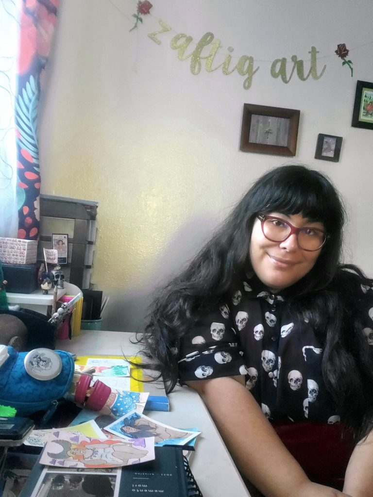 "Picture of Kristine sitting at her desk with a piece of artwork in front of her. She has long dark hair with bangs and is wearing red glasses and softly smiling at the camera. Above her are photos on the wall and a sign reading ""zaftig art""."