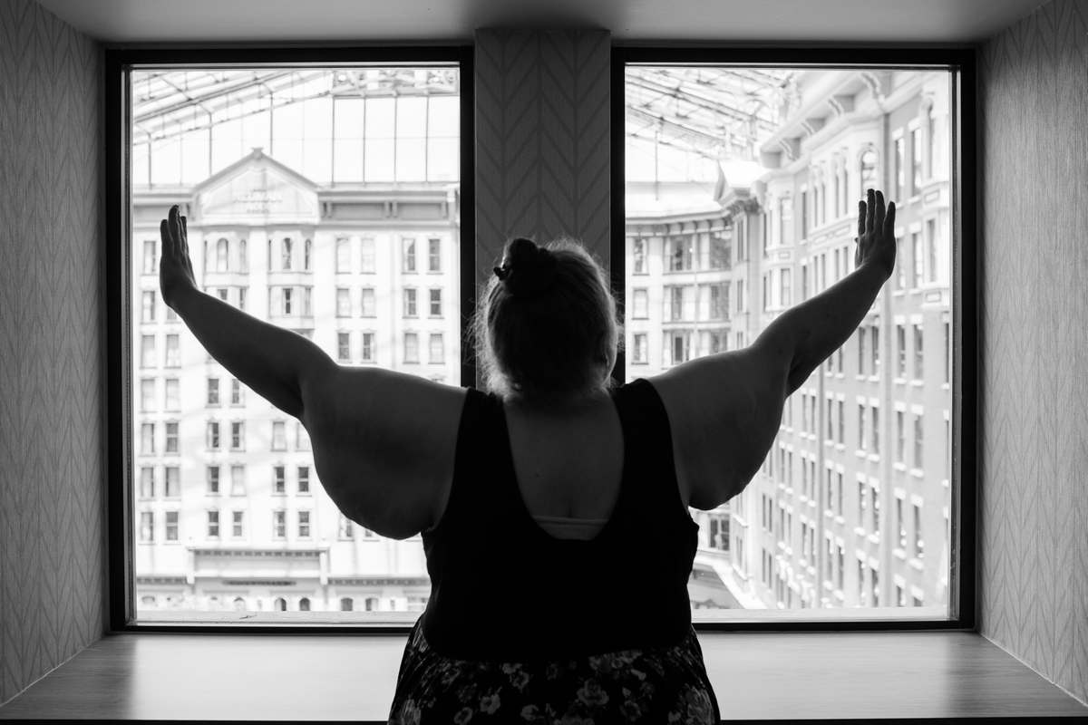 The woman in this photograph by Lindley Ashline has glorious wings on her arms that she lifts towards the ceiling, looking out a window into a large covered open space, in this black-and-white-photograph. She is fat, has long hair pinned into a bun and is wearing a sleeveless dress.
