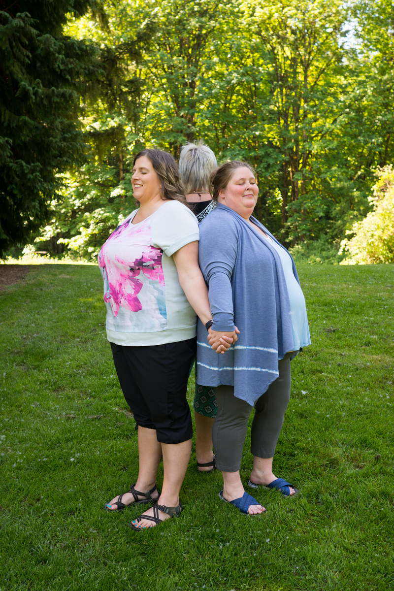 Three fat women stand back to back with hands entwined in a grassy park.