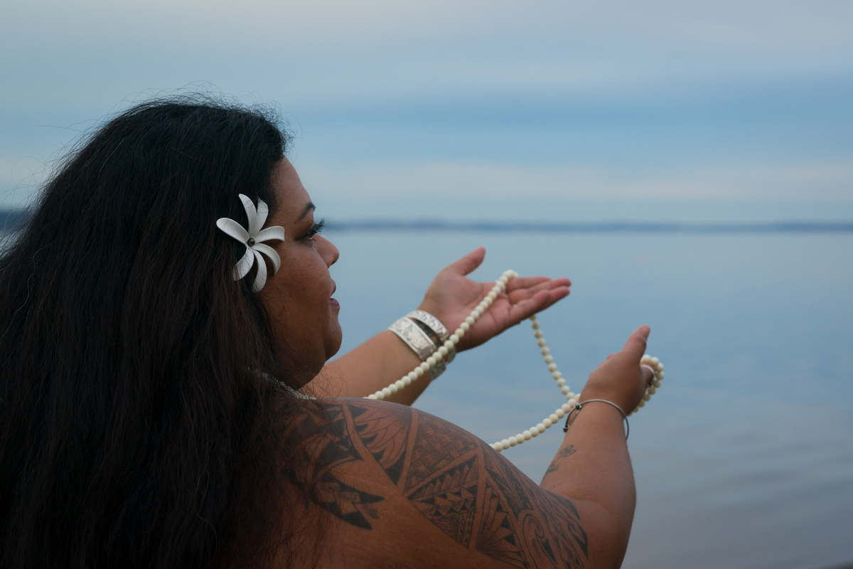 A fat Hawaiian woman with brown skin and black hair lifts a long pearl necklace toward a cloudy sky and blue water.