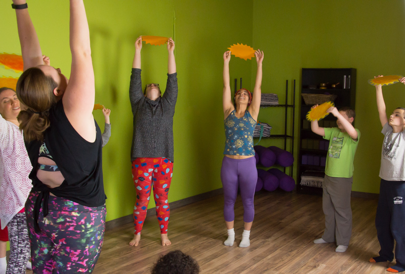 People in a family yoga class stretch their arms high, holding paper suns.