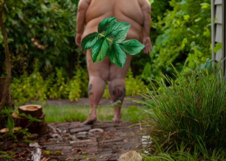 Image description: A nude fat woman with pale skin walks away down a garden path, a festival mask left discarded behind her.