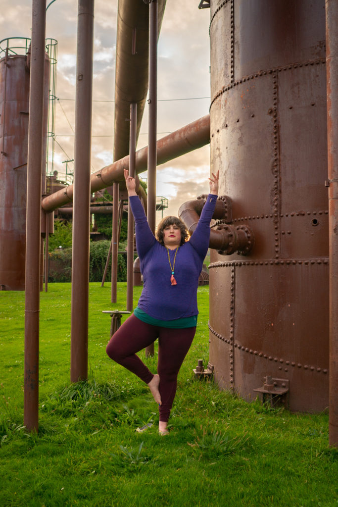 A fat woman does a tree yoga pose among large industrial pipes.