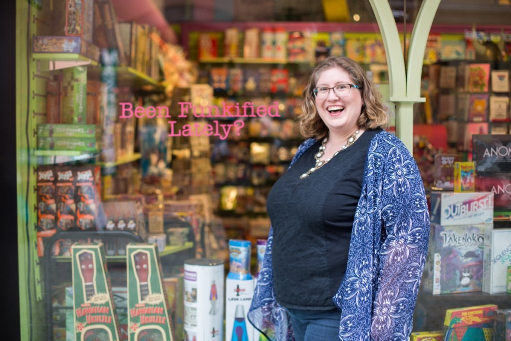 Lindley, a fat white woman, stands in front of a shop window that reads, Been Funkified?