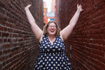Lindley, a fat white woman, stands in a narrow brick alley with her hands in the air.