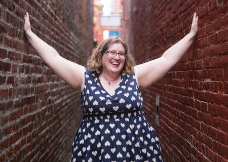 Lindley, a fat white woman, stands in a narrow brick alley with her hands on the walls.