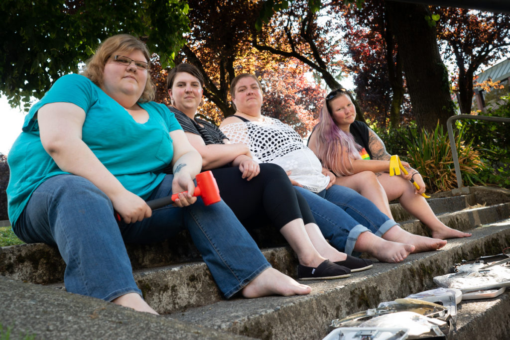 A group of people in larger bodies sit on concrete steps with hammers and smashed bathroom scales.