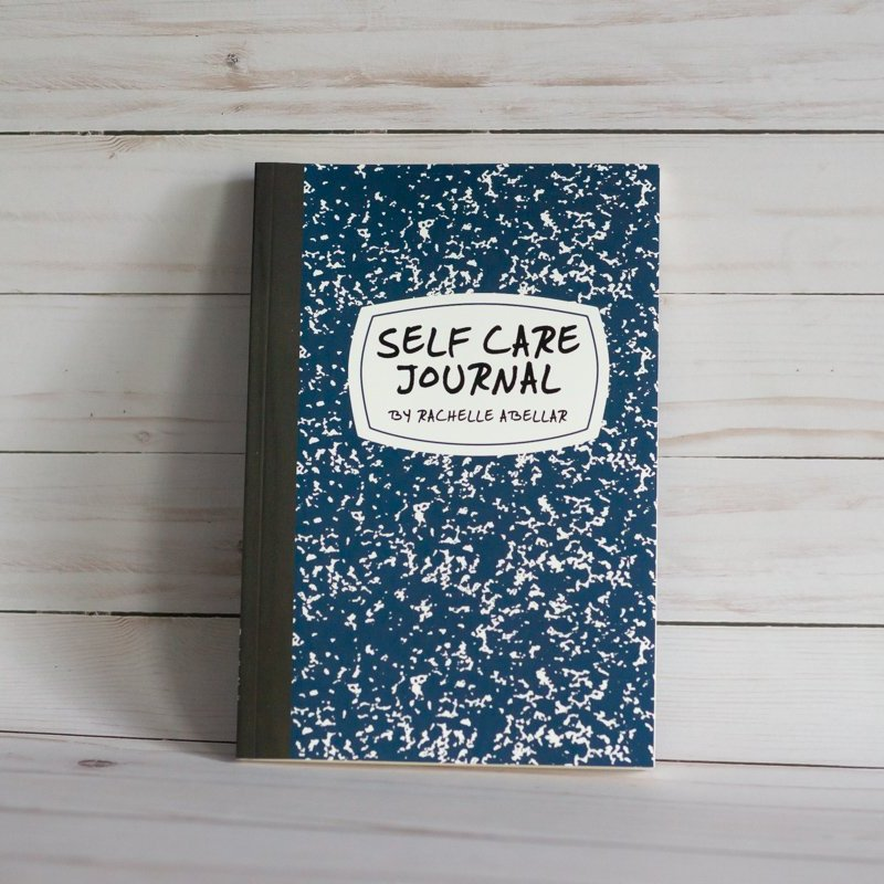 A book titled Self-Care Journal is shown on a white wooden background.