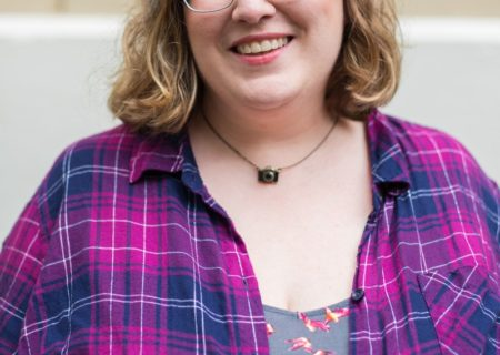 Lindley, a fat white woman, looking into the camera and smiling. She's wearing glasses, a pink and blue top and a camera necklace.