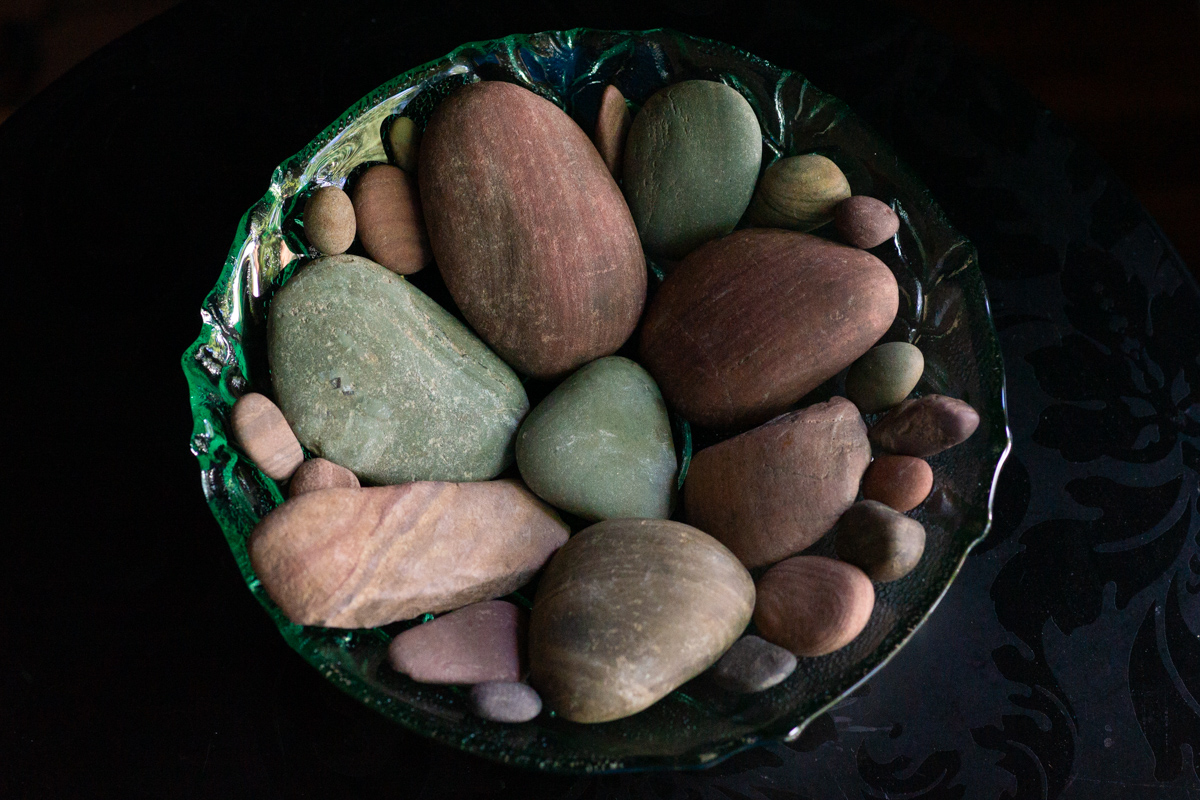 A green glass bowl of smooth pebbles in soft red and green tones and mixed sizes, stones Lindley found in a river in Idaho