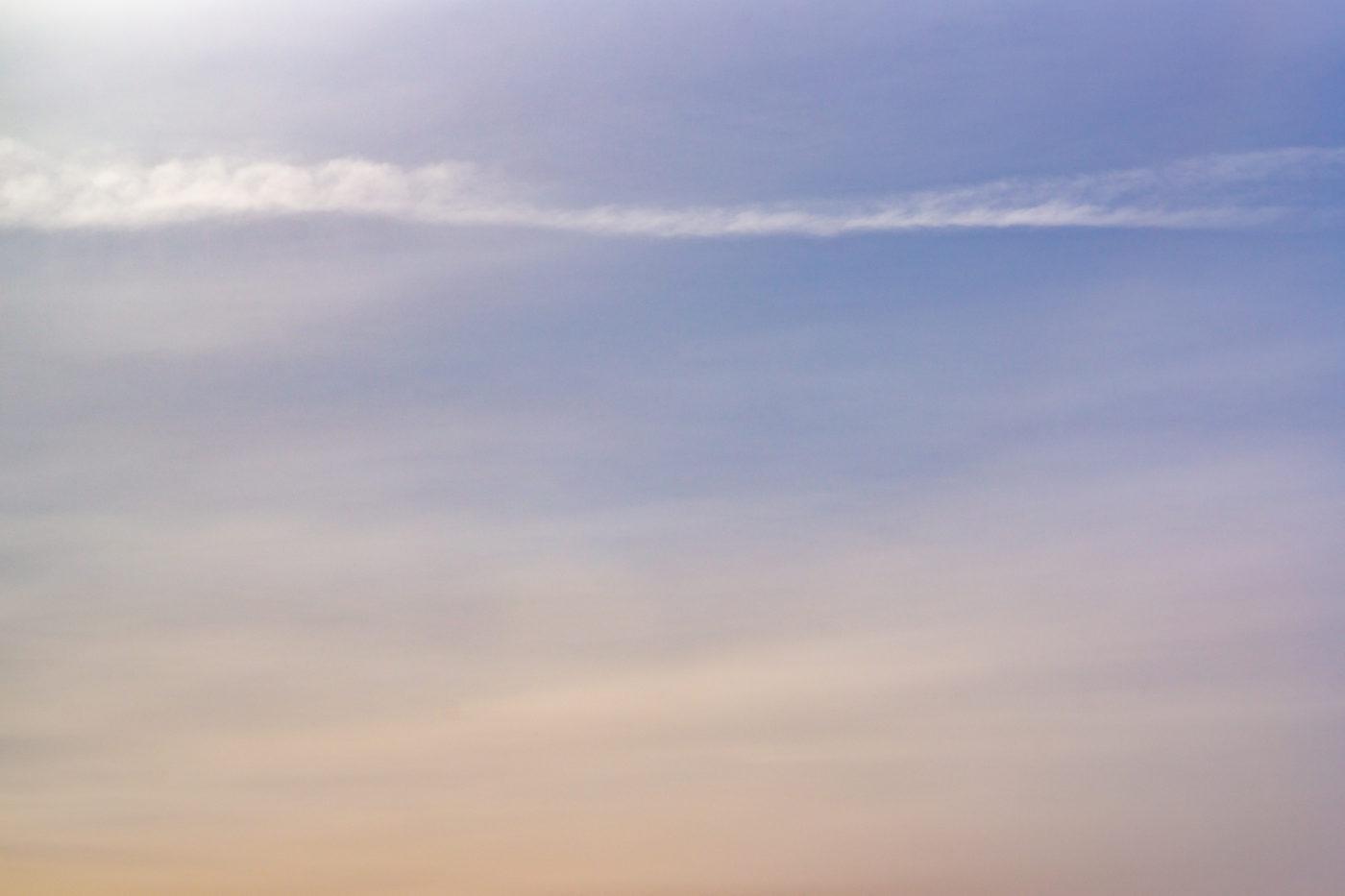 A blue and orange sky with soft misty cloud streaks.