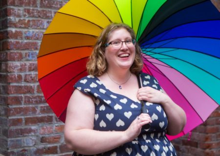 Image description: Lindley, a fat white woman, stands in front of a brick wall in a heart polka-dot dress. She's holding a rainbow umbrella and smiling.