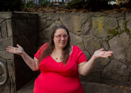 A fat white woman in a short-sleeved red dress sits in front of a stone wall and shrugs.
