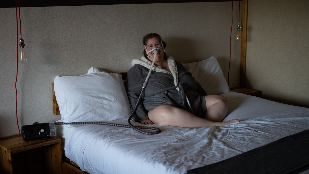 Lindley, a fat white woman in CPAP machine headgear and a gray robe, sits on a bed in a hotel room with white sheets and smiles.