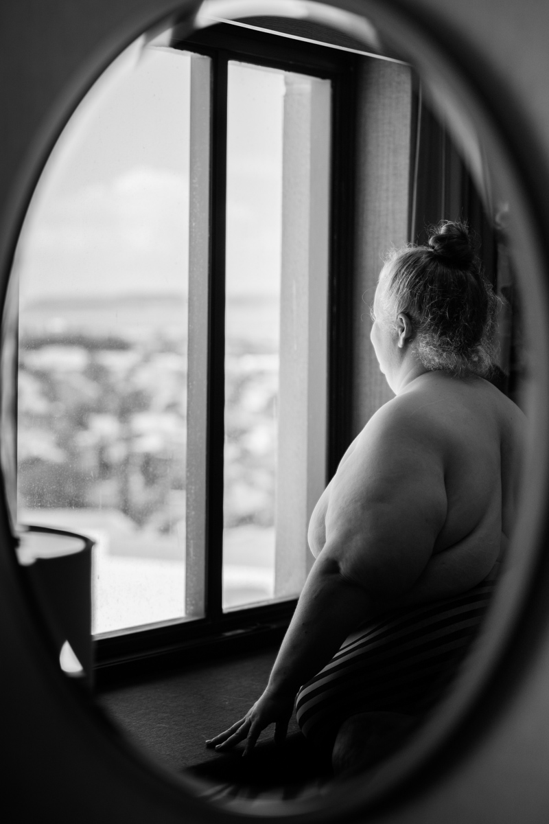 In this black and white photo, a fat white woman stands nude in front of a window high above a city and looks out, reflected in an oval mirror.