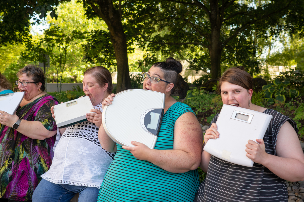 Four fat people in summer clothing hold bathroom scales and playfully bite them.