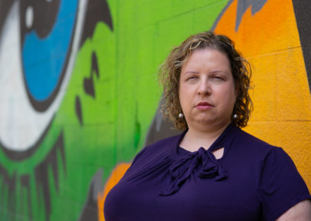 A woman with short curly hair, wearing a purple short-sleeved top, stands in front of a colorful mural with a neutral expression. She's gearing up to ask someone to stop dieting or being fatphobic.