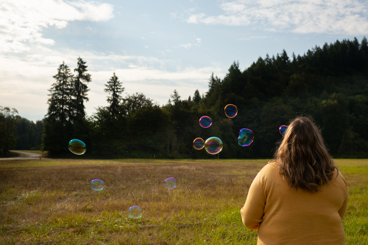 A fat woman with long brown hair and a yellow sweater blowing bubbles in a field. Her back is to the camera.