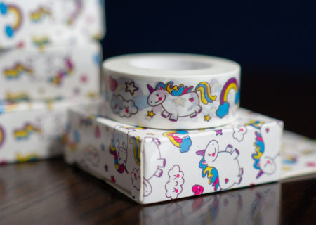 A roll of white washi tape with a cute unicorn design sitting on a similarly-patterned box, with a stack of more boxes in the background.