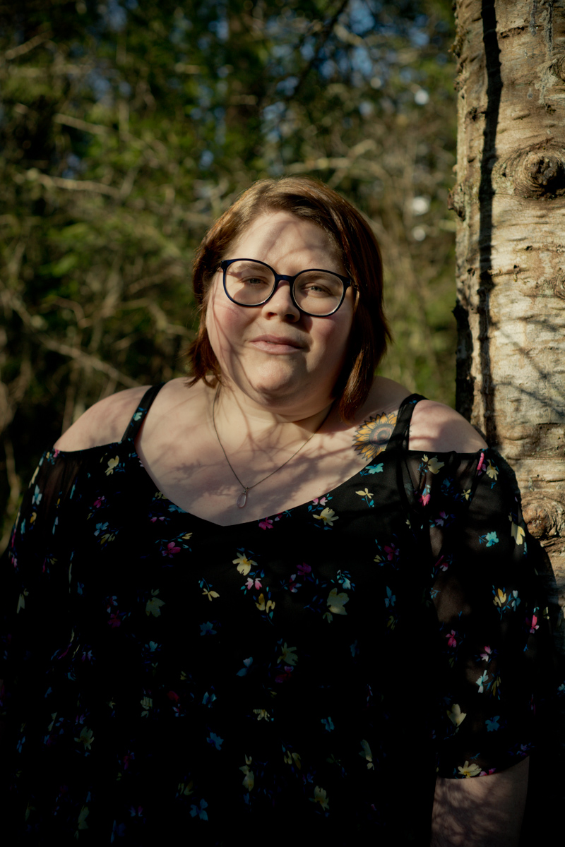 A fat white woman with glasses, short brown hair and a floral cold-shoulder top stands in a forest with shadows from tree branches crossing her face and a neutral expression.