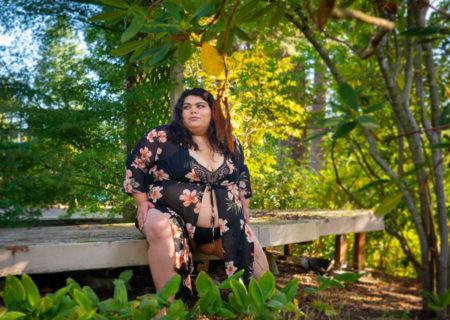 A fat woman with brown skin and black hair sits in a bra, panties and flowing robe on the edge of a wooden deck, surrounded by green plants, at a Seattle body-positive botanical boudoir photo session.