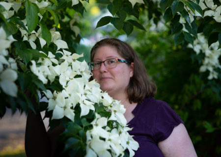 Lindley, a fat white woman with shoulder-length brown hair and glasses, stands in a garden at dusk holding a branch laden with white dogwood flowers.