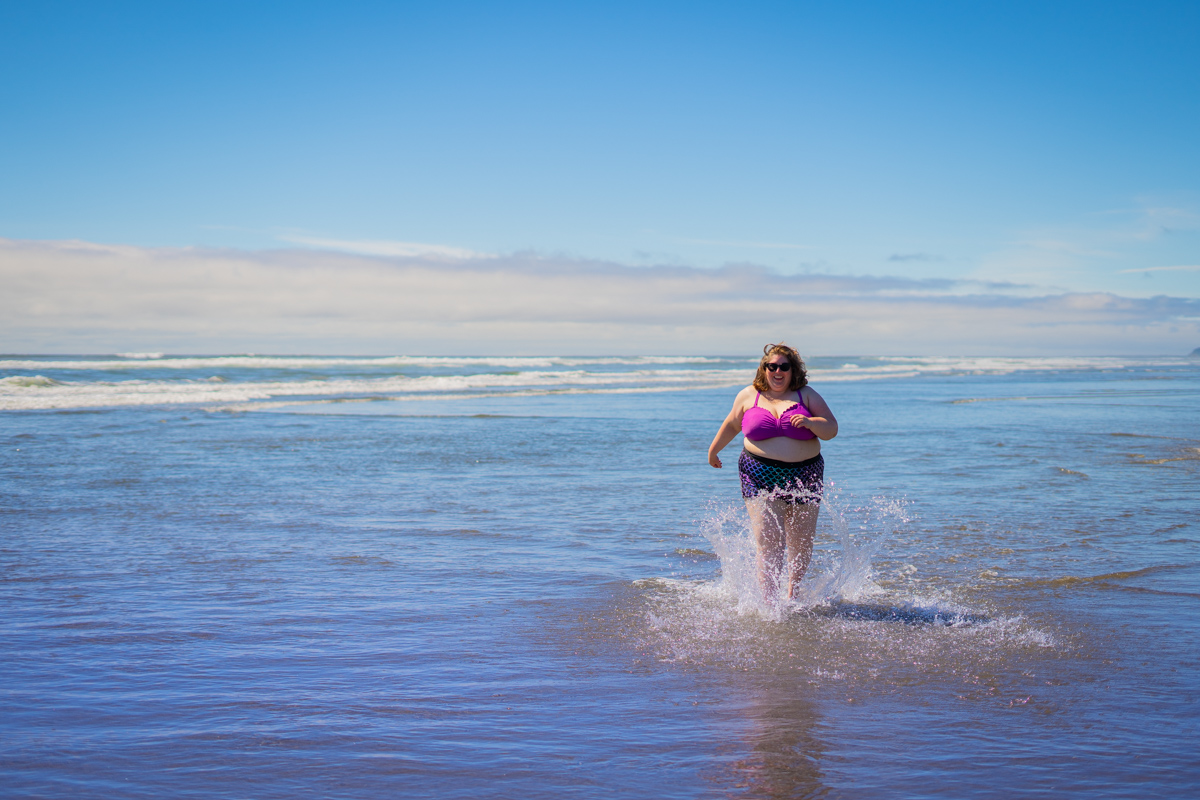 Lindley, a fat white woman in sunglasses and a two-piece swimsuit, splashes through shallow ocean water on a sunny day.