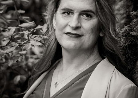 A black-and-white photo of a trans woman with long hair. She is wearing a v-neck blouse, blazer and necklace and is smiling gently in front of bushes.