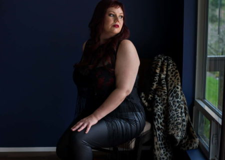 A woman with pale skin, black clothing and bright red boots sits in a chair in a darkish room, looking over her shoulder out the window. A leopardskin coat hangs from the chair back. She's at a body positive, plus size boudoir session in Seattle.