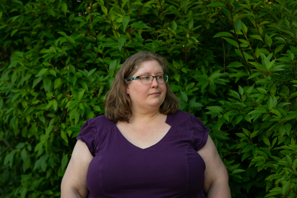 Lindley, a fat white woman in a purple dress and glasses, stands in front of green bushes and looks away from the camera. She looks annoyed, resigned or irritated.
