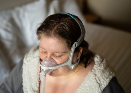 Lindley, a fat white woman in a fluffy gray and white robe, is sitting on a bed with her CPAP headgear and mask on and her eyes closed.