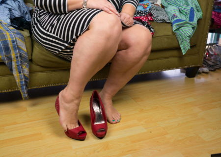 A fat person is shown from the waist down, wearing a striped dress and sitting on a couch in a plus-size clothing store. They're trying on red high-heeled shoes that are too small for their feet.