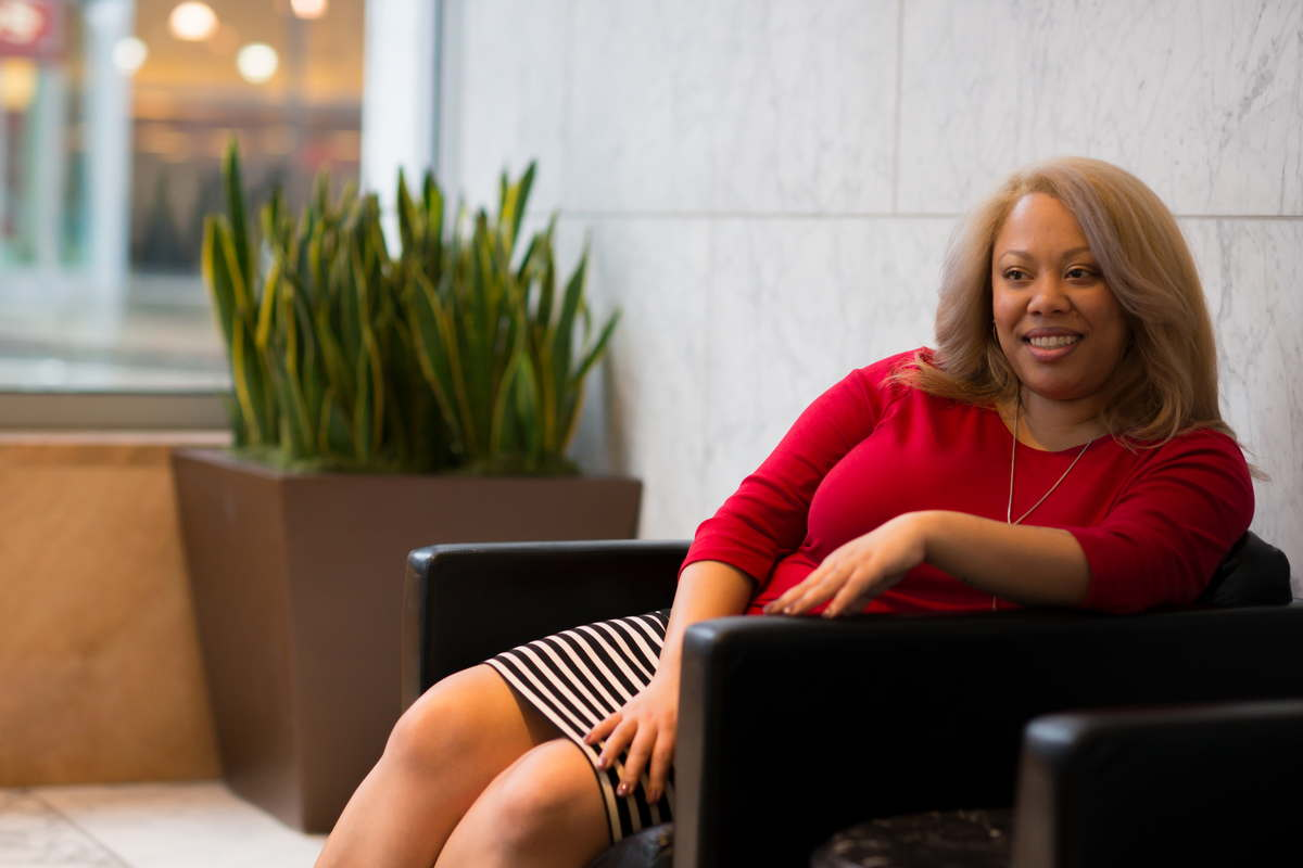 A plus-size Black woman in a striped skirt and red sweater sits in a leather chair in an office lobby, looking off to one side and smiling slightly.